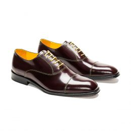 A custom made cap toe leather oxford shoe, bordeaux with yellow laces and green stitching. (Side 2 View)